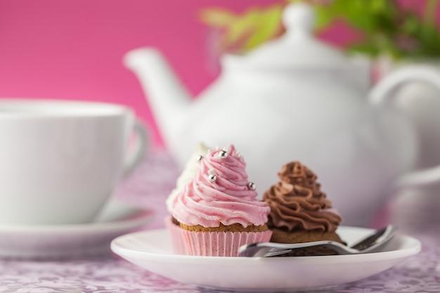 Cupcakes deliciosos com creme e jogo de chá