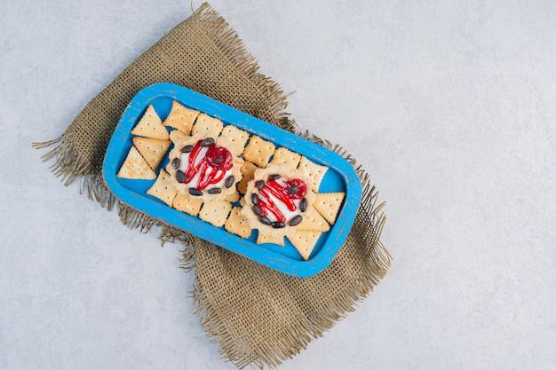 Cupcakes e biscoitos em uma bandeja azul na mesa de mármore.