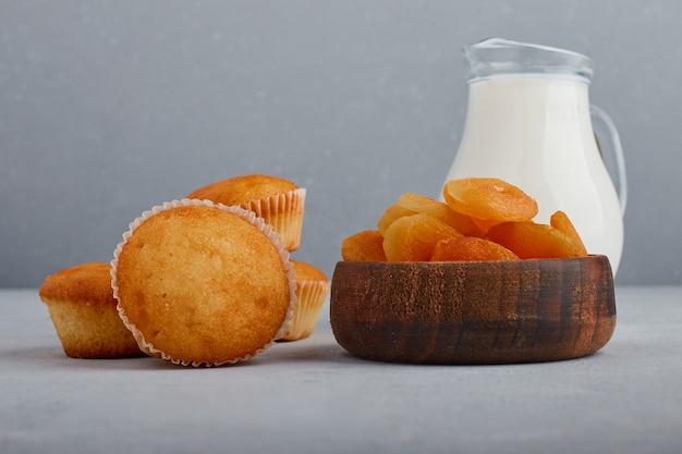 Cupcakes e damascos secos com uma jarra de leite.
