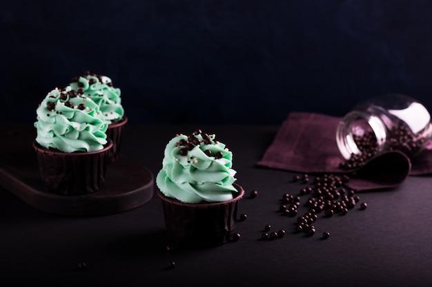 Cupcakes e granulado em uma superfície escura
