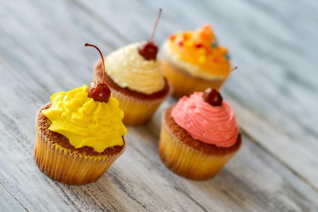 Cupcakes em fundo cinza creme amarelo e cereja para os amantes de doces guloseimas de sobremesa com baunilha ...