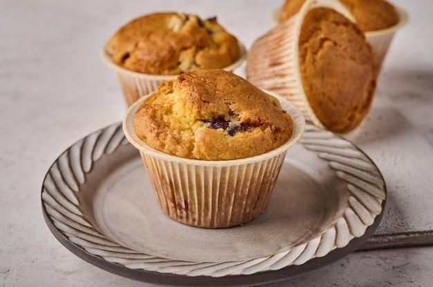 Cupcakes macro com cerejas no prato e foco seletivo de fundo claro