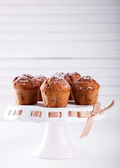 Cupcakes, muffins, pastelaria em um carrinho branco