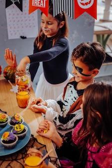 Cupcakes para o halloween. três crianças lindas e fofas comendo cupcakes enquanto fazem uma festa de halloween no jardim de infância