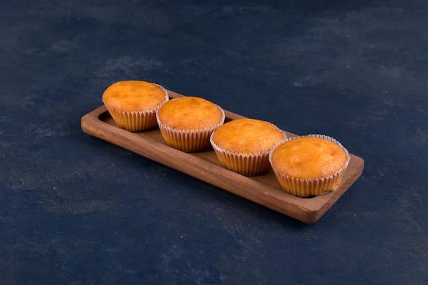 Cupcakes servidos em travessa estreita de madeira, vista panorâmica