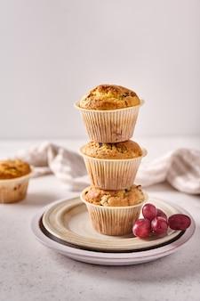Cupcakes um a um como pirâmide com cerejas e uvas no prato com guardanapo sobre fundo claro