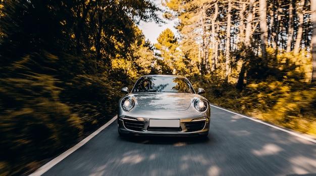 Cupê de cor prata com luzes dianteiras na estrada sob a luz do sol.
