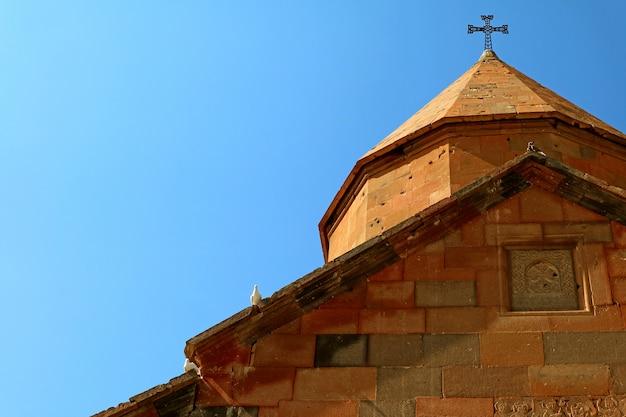 Cúpula da igreja ortodoxa armênia no céu ensolarado com três pombos empoleirados