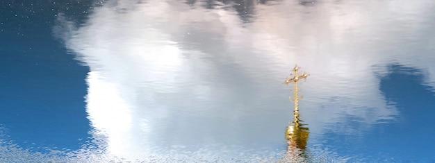 Cúpula dourada e ortodoxa cruz refletida na superfície da água