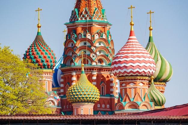 Cúpulas da catedral de são basílio na praça vermelha de moscou contra o céu azul e árvores verdes