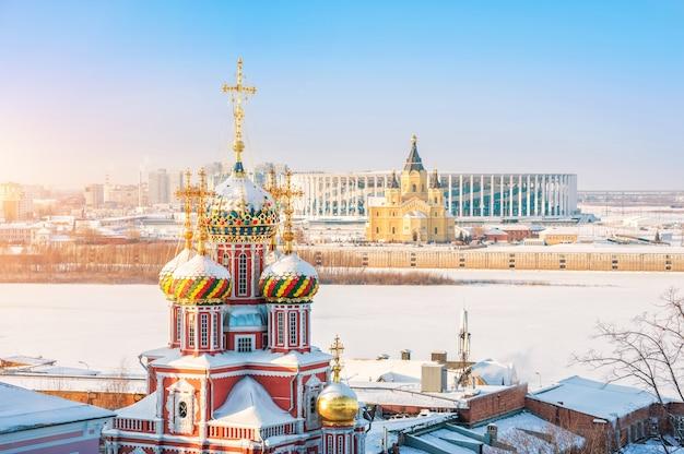 Cúpulas da igreja da natividade em nizhny novgorod e da catedral de alexander nevsky sob os raios do pôr do sol