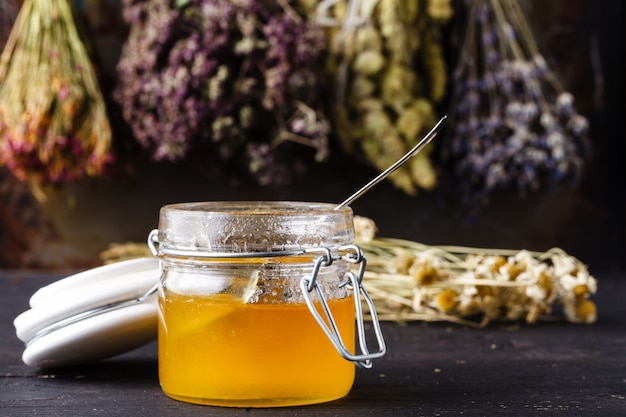 Cura de mel com ervas medicinais na parede escura