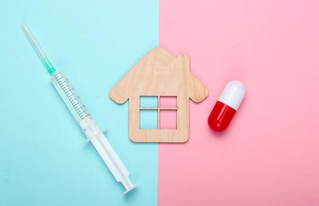Cura em casa. primeiros socorros em casa. estatueta de casa, seringa, cápsula em um fundo rosa azul pastel. vista do topo