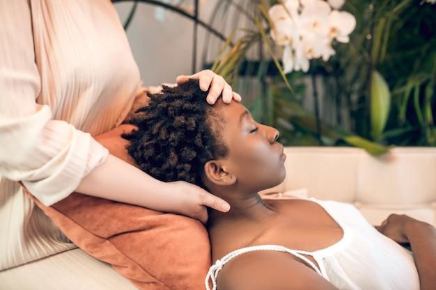 Cura. jovem curandeira trabalhando com uma paciente de pele escura em um salão ayurvédico