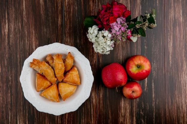 Curabier de vista superior em um prato com maçãs vermelhas e flores sobre fundo de madeira