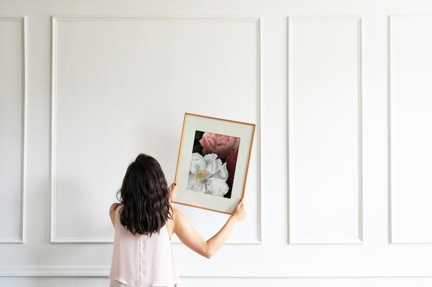 Curador pendurando moldura de arte floral na parede