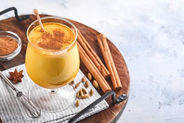Cúrcuma com leite dourado com canela em pau e mel. bebida ayurvédica saudável. bebida desintoxicante natural asiática da moda com especiarias para veganos. copie o espaço.