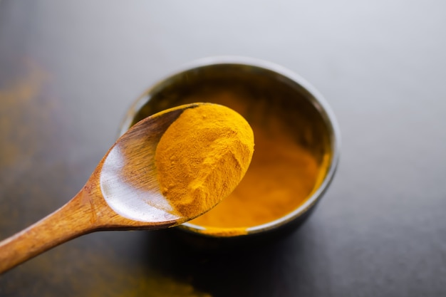 Cúrcuma em colher de pau no borrão cúrcuma em copo preto na mesa de madeira preta. erva orgânica tailandesa. a curcumina contém antioxidantes que ajuda a retardar o envelhecimento e as rugas.