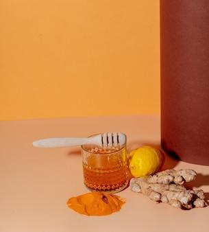 Cúrcuma, mel, limão e gengibre ao lado de um copo em um papel