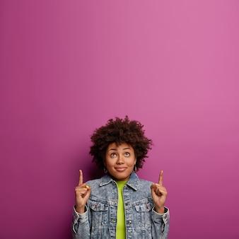 Curiosa e adorável mulher étnica com penteado encaracolado, apontando os dedos da frente para cima
