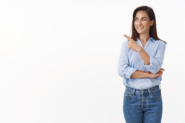 Curiosa e bonita mãe adulta se pergunta, fazendo uma pergunta, um recurso de produto interessante, uma vendedora curiosa falando, apontando olhando para a esquerda da copyspace, sorrindo, satisfeita, parede branca