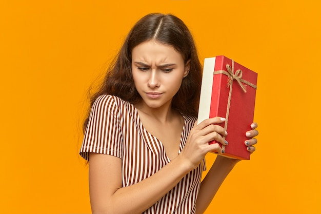 Curiosa e fofa garota em um lindo vestido listrado segurando uma caixa com fita dourada