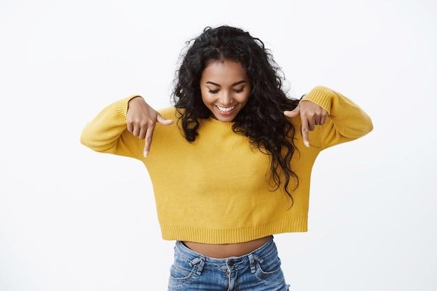 Curiosa e intrigada linda garota afro-americana feminina em um suéter amarelo apontando e olhando para baixo com um sorriso divertido, conferindo a incrível promoção, olhando para o anúncio, parede branca