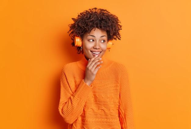 Curiosa e sorridente jovem encaracolada olhando de lado alegremente usando fones de ouvido estéreo ouve música favorita desfruta de uma melodia agradável vestida com um suéter casual isolado sobre uma parede laranja