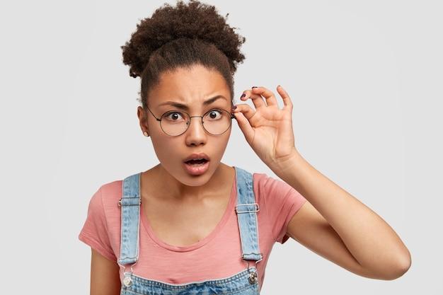 Curiosa e surpresa jovem de pele escura olha escrupulosamente através de óculos redondos, tem cabelo preto cacheado penteado em coque, olha atento para alguma coisa, usa macacão jeans com camiseta