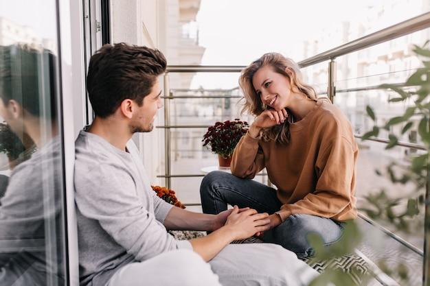 Curiosa garota caucasiana falando com um amigo no terraço. sonhadora jovem sentada na varanda com o namorado.