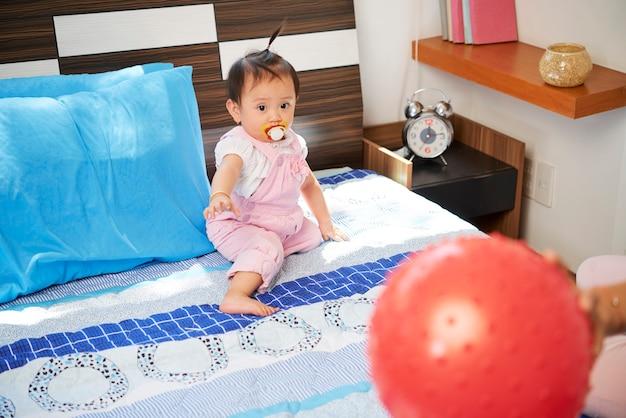Curiosa garotinha vietnamita com chupeta na boca, sentada na cama, olhando para uma bola vermelha brilhante na mão na mãe