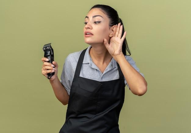 Curiosa jovem barbeira caucasiana vestindo uniforme segurando uma máquina de cortar cabelo, olhando para baixo, fazendo um gesto de não consigo ouvir você, isolado na parede verde oliva
