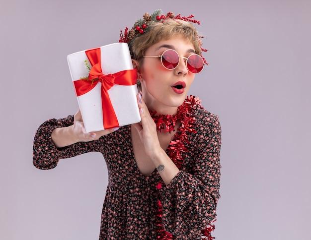 Curiosa jovem bonita usando coroa de natal na cabeça e guirlanda de ouropel em volta do pescoço, com óculos segurando um pacote de presente perto da cabeça, olhando para a câmera, isolada no fundo branco