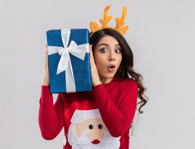 Curiosa, jovem e bonita garota usando bandana de chifres de rena e suéter de papai noel segurando um pacote de presente de natal perto da cabeça, isolada na parede branca com espaço de cópia