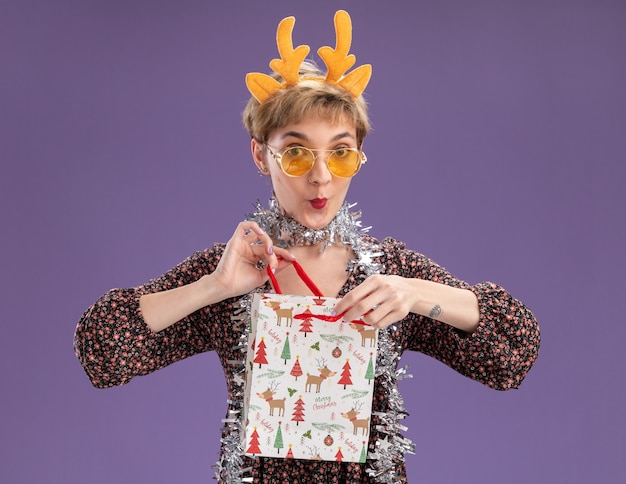 Curiosa, jovem e bonita garota usando uma faixa de chifres de rena e guirlanda de ouropel em volta do pescoço, com óculos segurando uma sacola de presente de natal, abrindo-a olhando para a câmera isolada no fundo roxo