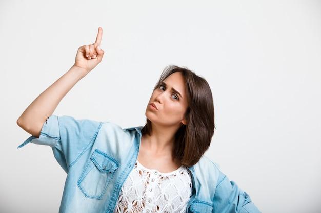 Curiosa mulher entusiasta apontando para cima