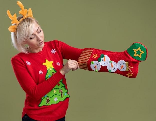 Curiosa mulher loira de meia-idade usando bandana de chifres de rena de natal e suéter de natal segurando e olhando a meia de natal, colocando a mão dentro dela isolada em fundo verde oliva
