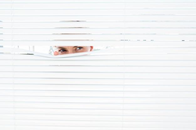 Curiosa mulher loira olhando através de persiana