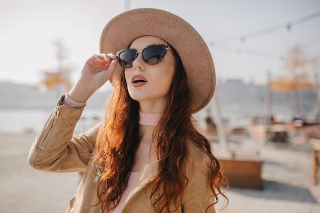 Curiosa mulher ruiva tocando seus óculos de sol