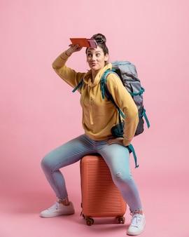 Curiosa mulher sentada na sua bagagem