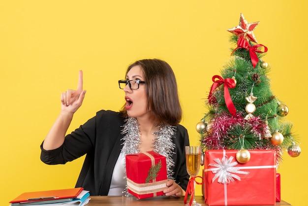 Curiosa senhora de negócios de terno com óculos segurando seu presente apontando para cima e sentada em uma mesa com uma árvore de natal no escritório