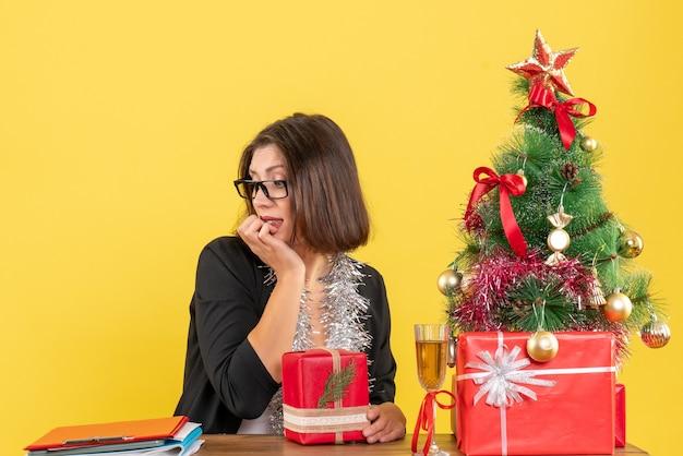 Curiosa senhora de negócios de terno com óculos segurando seu presente, olhando para baixo e sentada em uma mesa com uma árvore de natal no escritório