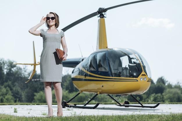 Curiosidade genuína. jovem encantadora empresária examinando o território de um heliporto durante uma excursão ao redor dele