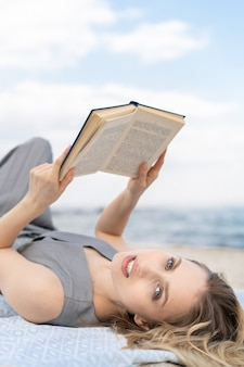 Curiosidades, jovem loira segurando um livro enquanto está deitado na praia