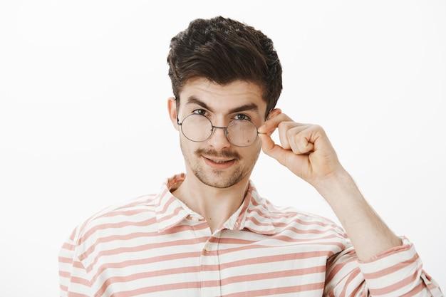 Curioso e interessante cara bonito olhando para uma grande coisa. satisfeito satisfeito homem atraente com barba e bigode, olhando por baixo da testa, tirando os óculos, olhando com interesse por cima da parede cinza