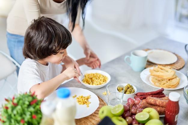 Curioso garotinho hispânico ajudando sua mãe a preparar uma refeição para o almoço, em pé na cozinha em casa juntos. maternidade, filhos, conceito de cozinha