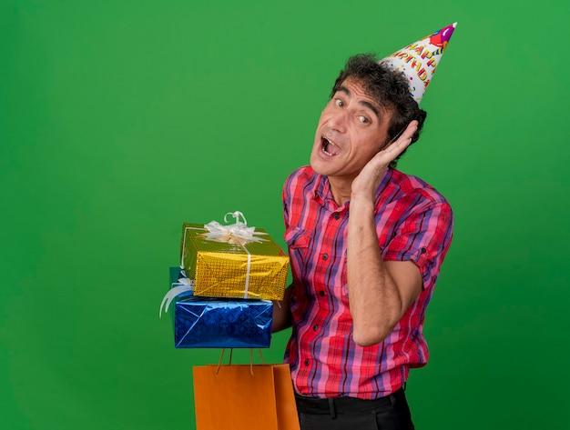 Curioso homem festeiro de meia-idade usando um boné de aniversário segurando pacotes de presentes e um saco de papel olhando para a frente fazendo um gesto de não consigo ouvir você isolado na parede verde