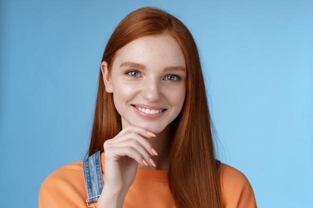 Curioso, inteligente, criativo, jovem, mulher ruiva, olhos azuis, tem uma ideia perfeita como passar as férias de verão sorrindo alegre olhar intrigado, pensativo, tocar o queixo pensando na escolha de pé fundo azul