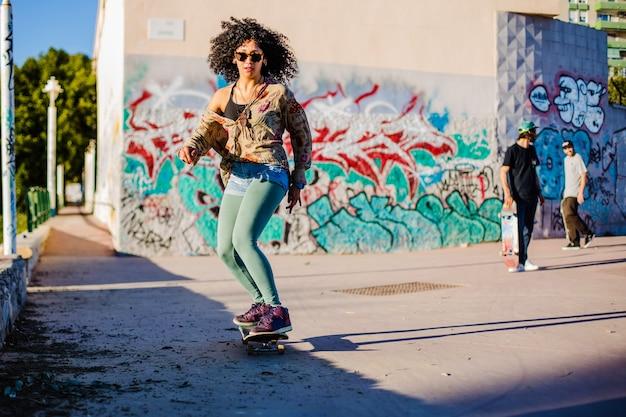 Curly haired brunette girl riding skateboard outside