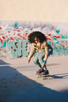 Curly haired morena menina andando skate encruzilhada
